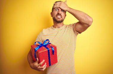 Man holding a present hesitantly