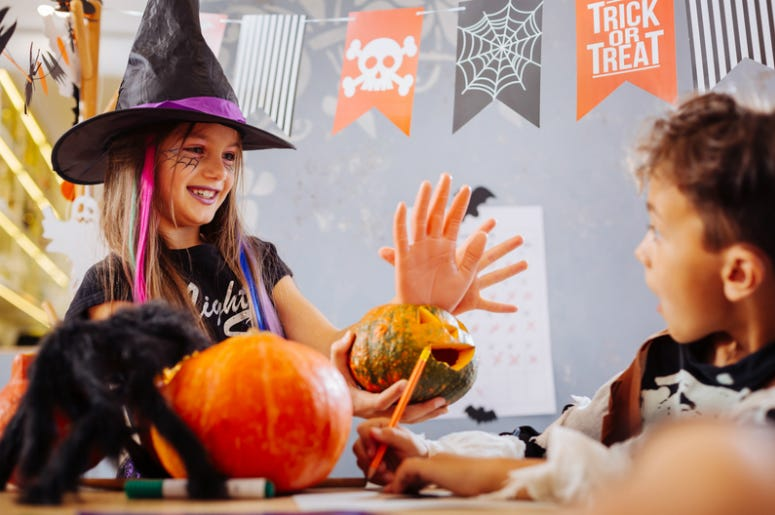 Funny sister wearing Halloween costume scaring brother with hand cookie
