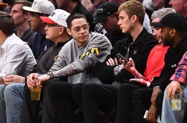comedian Pete Davidson (left) and American rapper Machine Gun Kelly (right) take in the game between the Charlotte Hornets against the Denver Nuggets during the second quarter at the Pepsi Center