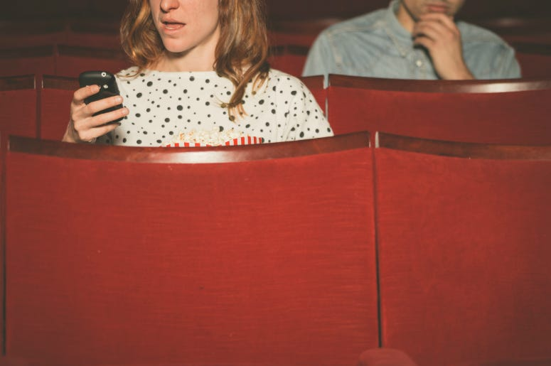 Woman using her phone in a theater as young man sitting behind her looks on.