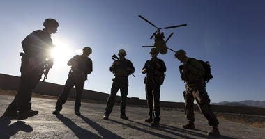 FILE - In this Nov. 30, 2017 file photo, American soldiers wait on the tarmac in Logar province, Afghanistan. Top officials in the White House were aware in early 2019 of classified intelligence indicating Russia was secretly offering bounties to the Tali