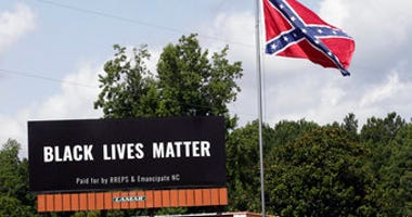 A Black Lives Matter billboard is seen next to a Confederate flag in Pittsboro, N.C., Thursday, July 16, 2020. A group in North Carolina erected the billboard to counter the flag that stands along the road. (AP Photo/Gerry Broome)