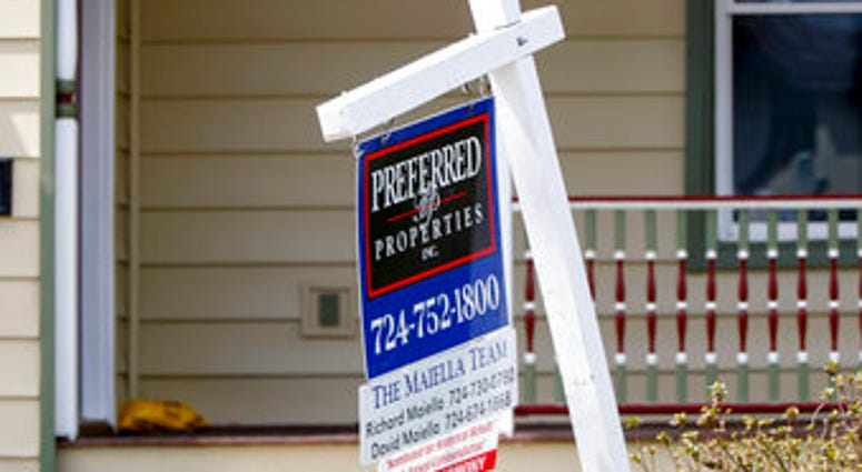 FILE This April 16, 2020 photo shows a real estate company sign marking a home for sale in Harmony, Pa. U.S. homeowners are seizing on historically low mortgage rates to refinance their mortgages. (AP Photo/Keith Srakocic)