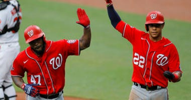 "Washington Nationals' Howie Kendrick (47) is greeted with ""air high fives"" by Juan Soto (22) after Kendrick scored them both on a two-run home run. (AP Photo/Julio Cortez)"