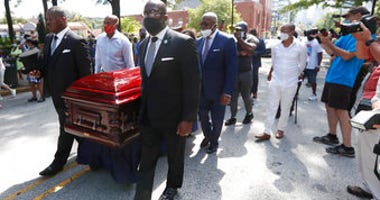 Mourners march with the casket of The Rev. C.T. Vivian to the Martin Luther King, Jr. National Historical Park during a memorial service for the Rev. Vivian, Wednesday, July 22, 2020, in Atlanta. (AP Photo/John Bazemore)