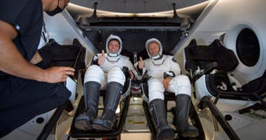 NASA astronauts Robert Behnken, left, and Douglas Hurley are seen inside the SpaceX Crew Dragon Endeavour spacecraft onboard the SpaceX GO Navigator recovery ship. (Bill Ingalls/NASA via AP)
