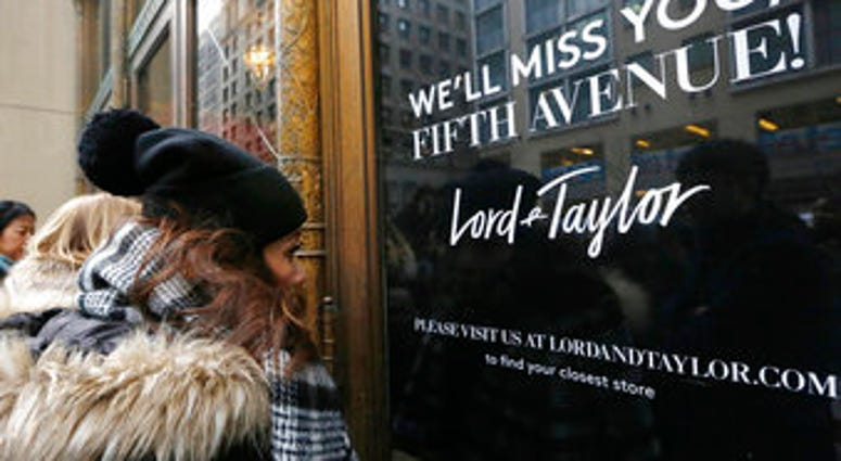 FILE - In this Jan. 2, 2019, file photo, women peer in the front door of Lord & Taylor's flagship Fifth Avenue store which closed for good in New York. (AP Photo/Kathy Willens, File)