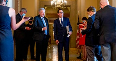 Treasury Secretary Steven Mnuchin, right, accompanied by White House chief of staff Mark Meadows, left, take a question from a reporter following a meeting with Senate Majority Leader Mitch McConnell of Ky. (AP Photo/Andrew Harnik)