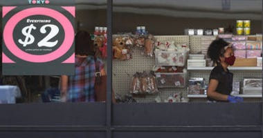 FILE - In this June 25, 2020 file photo, a price sign is displayed at a retail store as a store employee wears a mask while working in Niles, Ill.  (AP Photo/Nam Y. Huh, File)