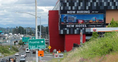 "FILE - In this July 9, 2020, file photo, a large video display reads ""Now hiring for our new hotel coming soon!,"" at the new Emerald Queen Casino, which is open, and owned by the Puyallup Tribe of Indians, in Tacoma, Wash.  (AP Photo/Ted S. Warren, File)"