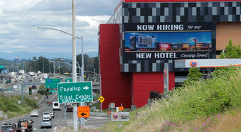 """FILE - In this July 9, 2020, file photo, a large video display reads """"Now hiring for our new hotel coming soon!,"""" at the new Emerald Queen Casino, which is open, and owned by the Puyallup Tribe of Indians, in Tacoma, Wash.  (AP Photo/Ted S. Warren, File)"""