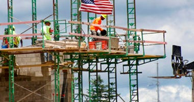 FILE - In this June 11, 2020 file photo, workers on scaffolding lay blocks on one of the larger buildings at a development site where various residential units and commercial sites are under construction. (AP Photo/Keith Srakocic, File)