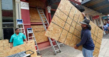Cesar Reyes carries a sheet of plywood to cut to size as he and Robert Aparicio, left, and Manuel Sepulveda install window coverings at Strand Brass and Christmas on the Strand in Galveston. ( Jennifer Reynolds/The Galveston County Daily News via AP)