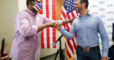 Donald Trump Jr., right, meets with congressional candidate Burgess Owens and volunteers at Colonial Flag in Sandy, Utah, Thursday, July 23, 2020.  (Jeffrey D. Allred/The Deseret News via AP)