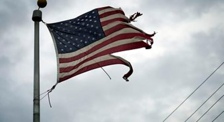 A tattered American flag blows in the wind in the aftermath of Hurricane Laura Thursday, Aug. 27, 2020, in Port Arthur, Texas. (AP Photo/Eric Gay)