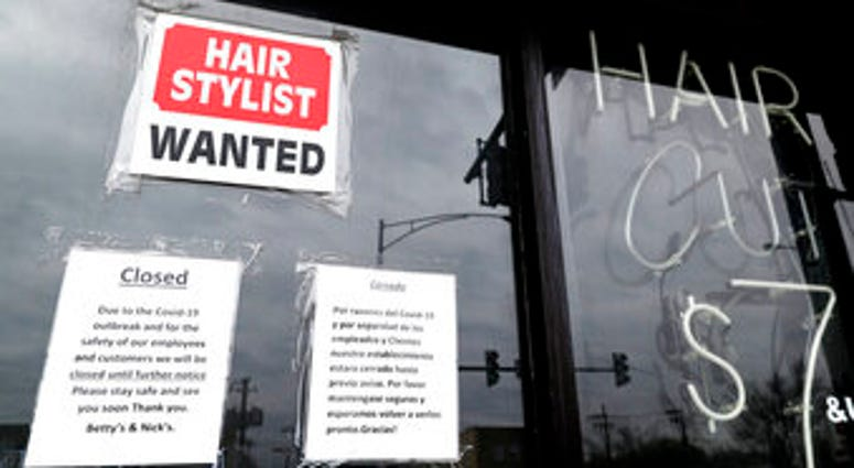 FILE - In this April 30 ,2020 file photo, a barber shop shows closed and hiring sign during the COVID-19 in Chicago. (AP Photo/Nam Y. Huh, File)