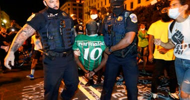 Metropolitan Police carry away a handcuffed protestor along a section of 16th Street, Northwest, renamed Black Lives Matter Plaza, Thursday night , Aug. 27, 2020, in Washington. (AP Photo/Julio Cortez)