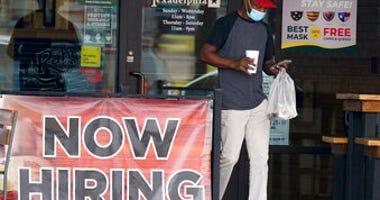 FILE - In this Sept. 2, 2020, file photo, a customer walks past a now hiring sign at an eatery in Richardson, Texas. The Labor Department reported unemployment numbers Thursday, Sept. 3. (AP Photo/LM Otero, File)