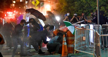 Police spray an irritant at demonstrators outside the Public Safety Building in Rochester, N.Y., Thursday, Sept. 3, 2020. (AP Photo/Adrian Kraus)