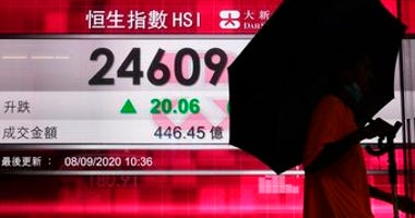 A man wearing a face mask walks past a bank's electronic board showing the Hong Kong share index in Hong Kong, Tuesday, Sept. 8, 2020. (AP Photo/Vincent Yu)