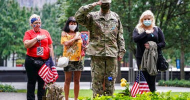 U.S. Army Sgt. Edwin Morales, center right, salutes after placing flowers for fallen FDNY firefighter Ruben D. Correa at the National September 11 Memorial and Museum, Friday, Sept. 11, 2020, in New York. (AP Photo/John Minchillo)