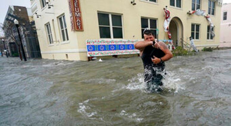 Trent Airhart wades through floodwaters, Wednesday, Sept. 16, 2020, in downtown Pensacola, Fla. (AP Photo/Gerald Herbert)
