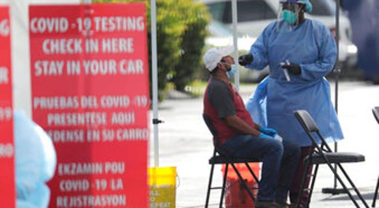 FILE - In this July 6, 2020 file photo, a health care worker administers a COVID-19 test at a site sponsored by Community Heath of South Florida at the Martin Luther King, Jr. Clinica Campesina Health Center in Homestead, Fla.(AP Photo/Lynne Sladky, File)