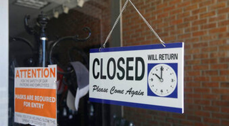 FILE - In this July 18, 2020 file photo a closed sign hangs in the window of a barber shop in Burbank, Calif. (AP Photo/Marcio Jose Sanchez, File)