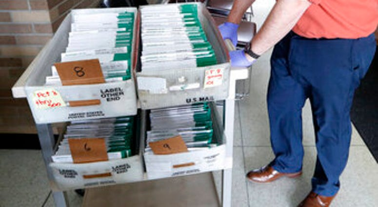 FILE - In this May 5, 2020, file photo, absentee ballots to be counted are moved at City Hall in Garden City, Mich. (AP Photo/Paul Sancya, File)