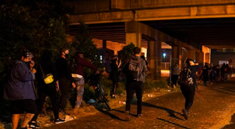 Protesters react to gunfire, Wednesday, Sept. 23, 2020, in Louisville, Ky. (AP Photo/John Minchillo)