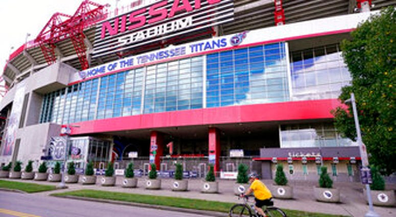 A cyclist passes by Nissan Stadium, home of the Tennessee Titans, Tuesday, Sept. 29, 2020, in Nashville, Tenn. (AP Photo/Mark Humphrey)