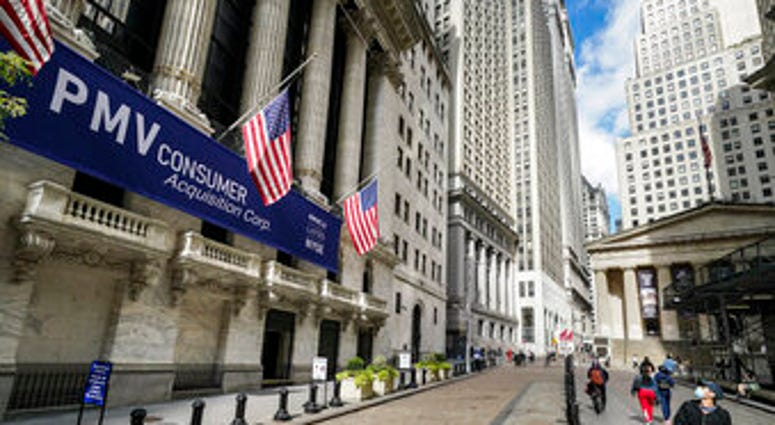 FILE - Pedestrians pass the New York Stock Exchange, Friday, Oct. 2, 2020, in New York. Stocks are opening broadly higher on Wall Street, following global markets higher on Election Day in the U.S. (AP Photo/John Minchillo)