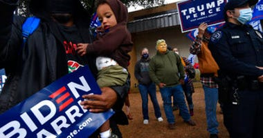 Demetrius Earthly balances his one-year-old son Brodrick and a Biden-Harris campaign sign, Wednesday, Oct. 28, 2020. Behind him, Toby Lindley wears a Donald Trump mask. (Ronald W. Erdrich/The Abilene Reporter-News via AP)