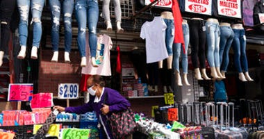 FILE - In this Sept. 25, 2020 file photo, a woman shops at a clothing store in New York. (AP Photo/Mark Lennihan, File)