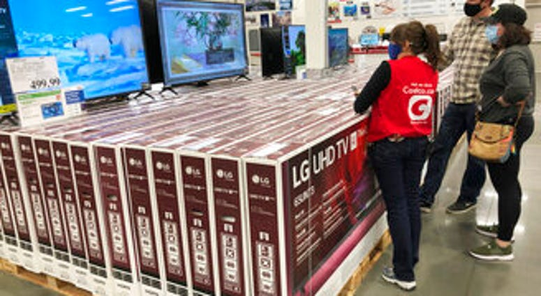 A sales associate helps customers as they consider the purchase of a big-screen television at a Costco warehouse on Wednesday, Nov. 18, 2020, in Sheridan, Colo.  (AP Photo/David Zalubowski)