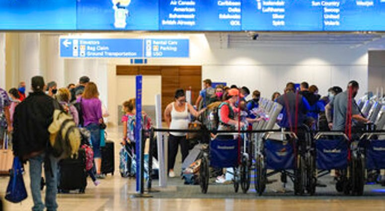 Holiday travelers check in at kiosks near an airline counter at Orlando International Airport Tuesday, Nov. 24, 2020, in Orlando, Fla. (AP Photo/John Raoux)