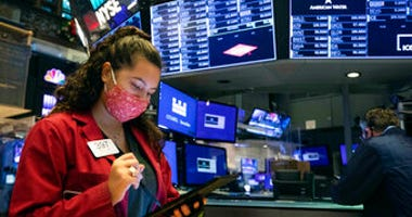 In this photo provided by the New York Stock Exchange, trader Ashley Lara uses her handheld device as she works on the trading floor, Tuesday, Dec. 1, 2020. (Colin Ziemer/New York Stock Exchange via AP)