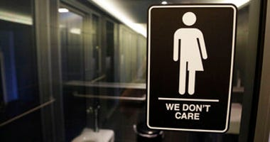 FILE - In this May 12, 2016, file photo, gender free sign hangs outside a restroom at 21c Museum Hotel in Durham, N.C. (AP Photo/Gerry Broome, File)