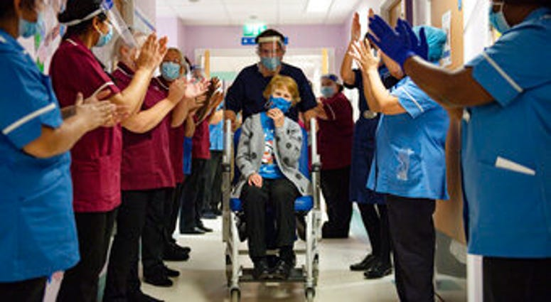 Margaret Keenan, 90, is applauded by staff as she returns to her ward after becoming the first patient in the UK to receive the Pfizer-BioNTech COVID-19 vaccine. (Jacob King/Pool via AP)