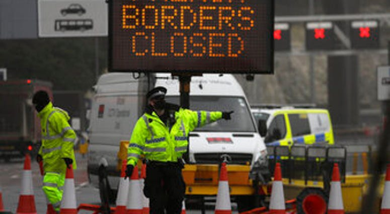 A police officer directs traffic at the entrance to the closed ferry terminal in Dover, England, Monday, Dec. 21, 2020. (AP Photo/Kirsty Wigglesworth)