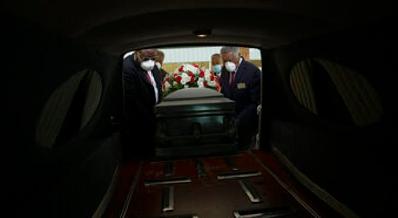 FILE - In this Saturday, April 18, 2020 file photo, a casket is placed into a hearse. (AP Photo/Brynn Anderson)