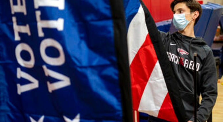 Thomas Hedrich sets up voting flags at a polling location in Gwinnett County, Ga., outside of Atlanta on Monday, Jan. 4, 2021, in advance of the Senate runoff election. (AP Photo/Ben Gray)