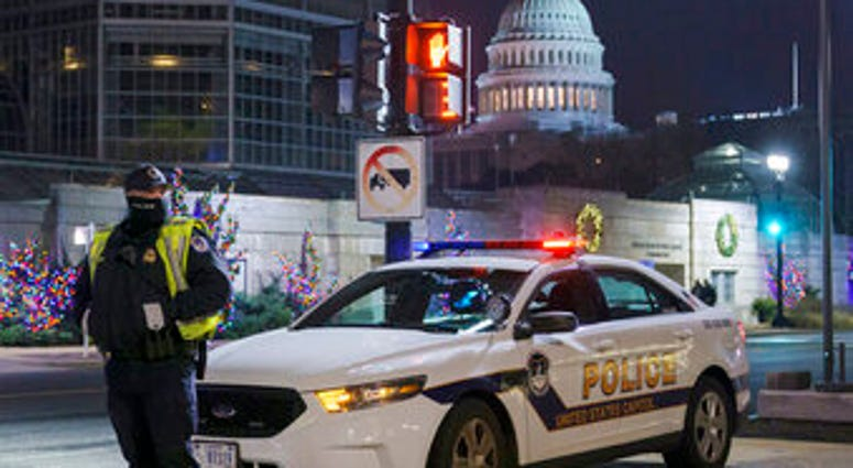 A U.S. Capitol Police officer stands watch on Independence Avenue before dawn as the House and Senate prepare to convene a joint session to count the electoral votes cast in November's election. (AP Photo/J. Scott Applewhite)