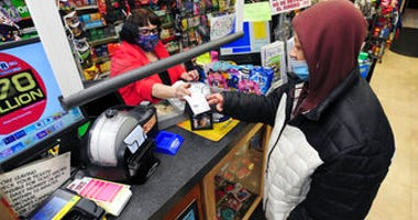 Jacqueline Donahue of Hazleton, right, buys la Mega Millions lottery ticket at the Anthracite Newsstand on Public Square, Monday, Jan. 18, 2021, in Wilkes-Barre, Pa. (Mark Moran/The Citizens' Voice via AP)