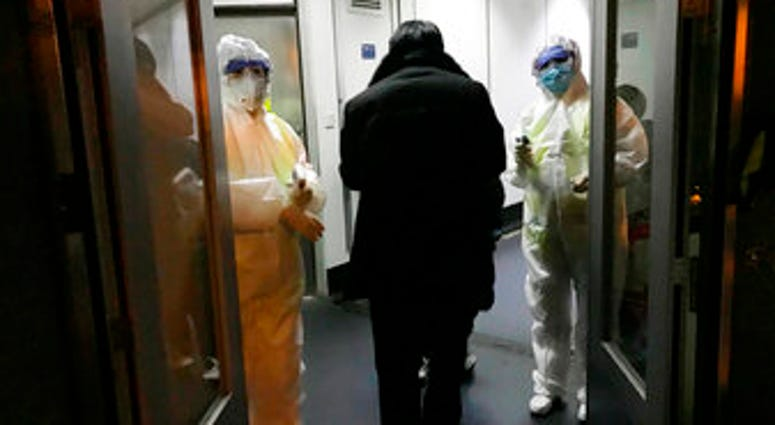 FILE - In this Wednesday, Jan. 22, 2020 file photo, Health Officials in hazmat suits wait at the gate to check body temperatures of passengers arriving from the city of Wuhan, at the airport in Beijing, China. (AP Photo Emily Wang, File)