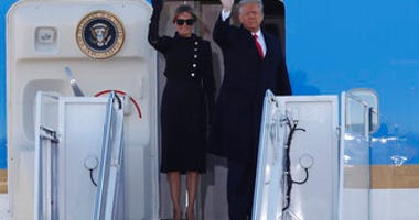 President Donald Trump and first lady Melania Trump wave to a crowd as they board Air Force One at Andrews Air Force Base, Md., Wednesday, Jan. 20, 2021. (AP Photo/Luis M. Alvarez)