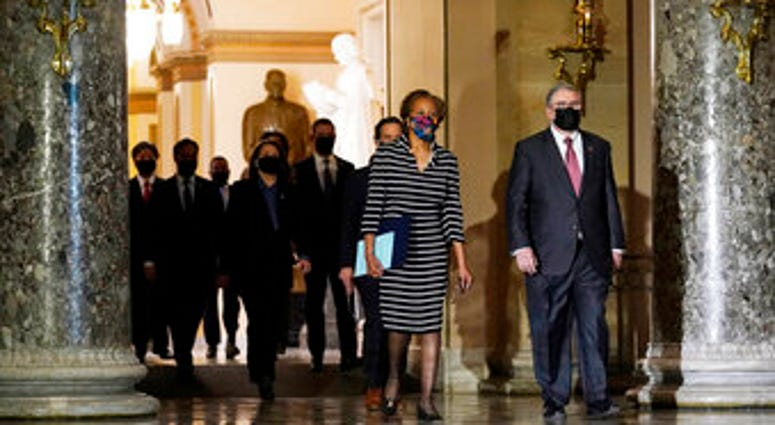 Clerk of the House Cheryl Johnson along with acting House Sergeant-at-Arms Tim Blodgett, lead the Democratic House impeachment managers as they walk through Statuary Hall in the Capitol. (AP Photo/Susan Walsh)