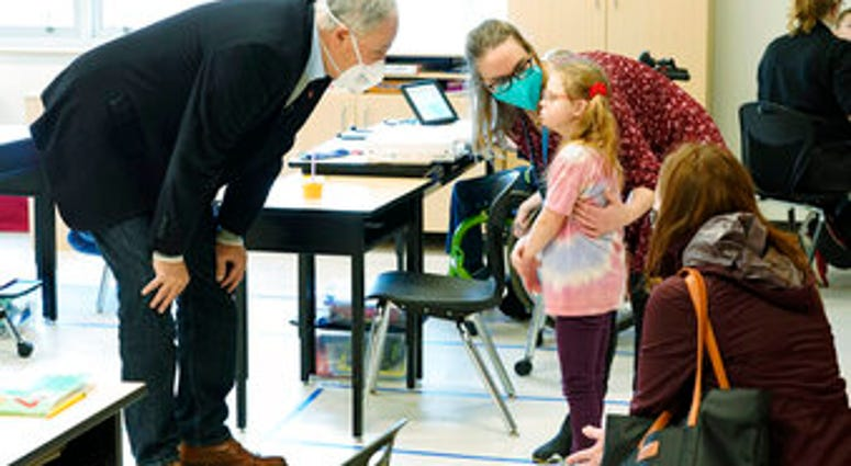 Washington Gov. Jay Inslee, left, talks with a student as teacher Alyson Lykken, center, looks on, Tuesday, Feb. 2, 2021, during a visit to a low-incidence disability classroom at Elk Ridge Elementary School in Buckley, Wash. (AP Photo/Ted S. Warren)