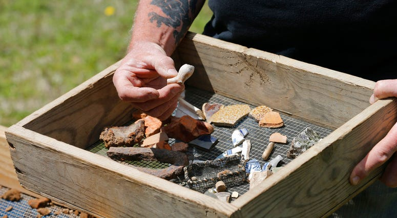 In this April 10, 2018 photo, a Jamestown Rediscovery Foundation archeologist shows artifacts and discusses what they know about one of the first enslaved Africans to live in English North America in Jamestown, Va.(AP Photo/Steve Helber)