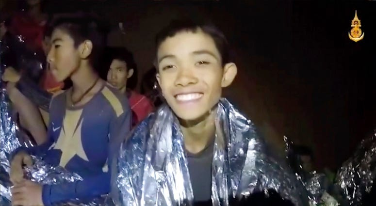 In this July 3, 2018, image taken from video provided by the Royal Thai Navy Facebook Page, Thai boys smile as Thai Navy SEAL medic help injured children inside a cave in Mae Sai, northern Thailand. (Royal Thai Navy Facebook Page via AP)